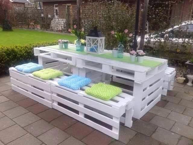 Mesa y bancos de terraza hechos con palets pintados de blanco.