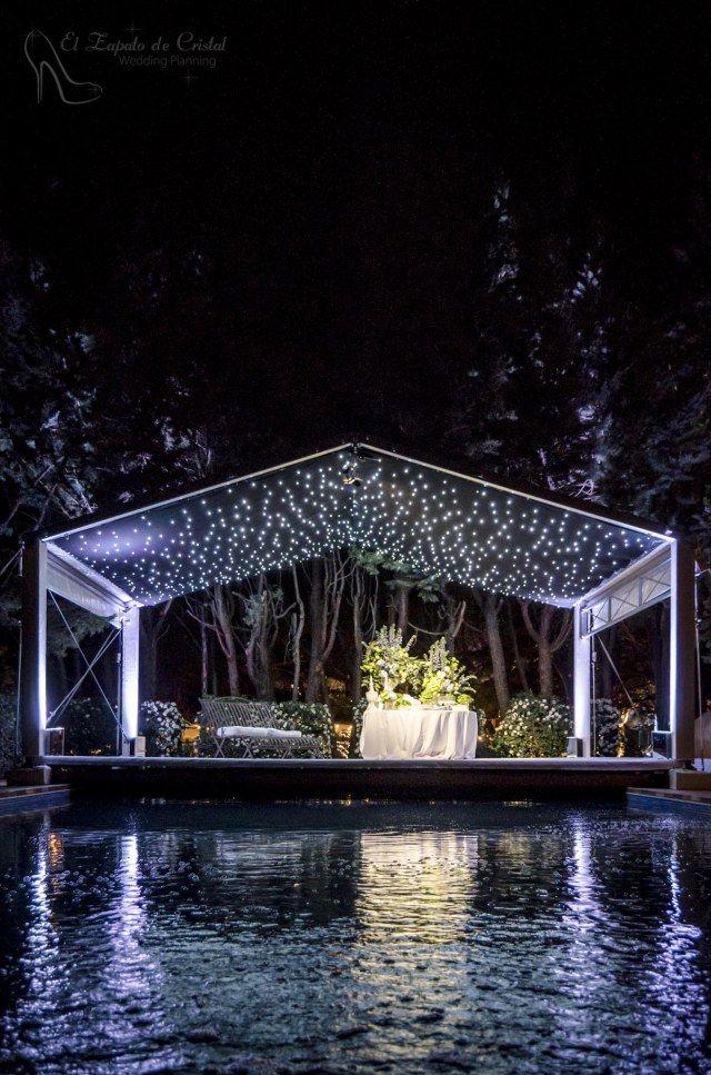 Carpa con plataforma sobre piscina con techo de estrellas. Pool night wedding decoration.