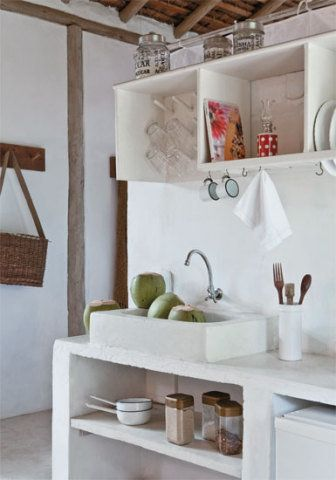 Na cozinha, soluções simples, como a bancada de concreto pintada de branco e os armários feitos com caixotes. A ideia para pendurar os copos em pinos de madeira veio dos botecos da região.