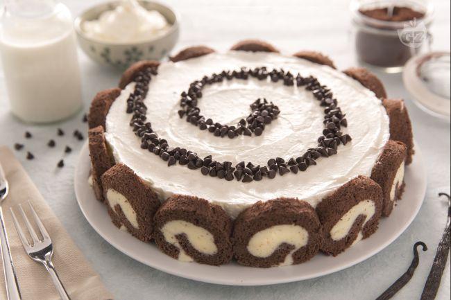 La cheesecake swiss roll è un dessert composto da una cheesecake leggera e un rotolo al cioccolato tagliato a fettine per decorare tutto il perimetro