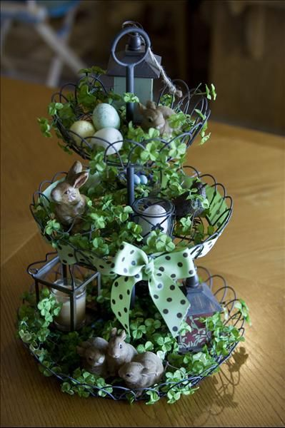 French Wire stand with woven ribbon through the second tier and clover strands in all three tiers, with several bunnies, birds nests, eggs, and the Birdhouse Trio, and the Firefly Lantern. Willowhouse