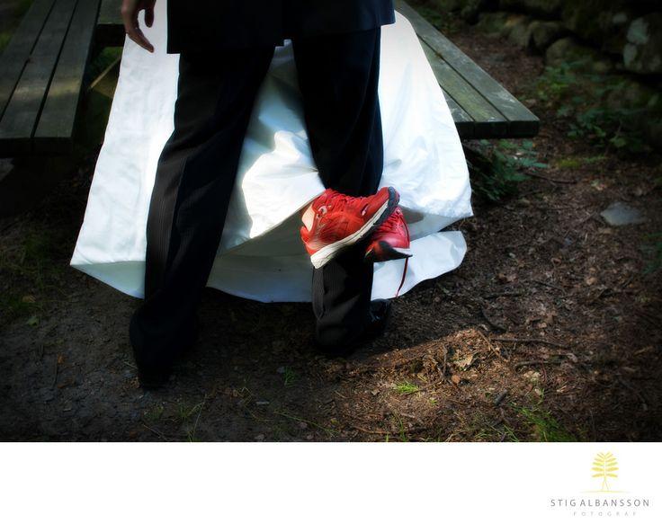 Företagsfoto - Porträttfoto - Bröllopsfotograf - Röda gympaskor och vit brudklänning omfamnar brudgum: Brud med röda gympaskor och vit brudklänning omfamnar brudgums ben i Västerskog i Särö Location: Västerskog, Särö.