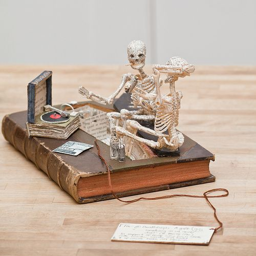 """A pair of skeletons perched on a coffin lid, clearly having a good time drinking, smoking and listening to music. By their feet is a crate of bottles and next to them is a turntable and a record sleeve reading """"THE IMPOSSIBLE DEAD / IAN RANKIN / SOME SECRETS NEVER DIE"""""""