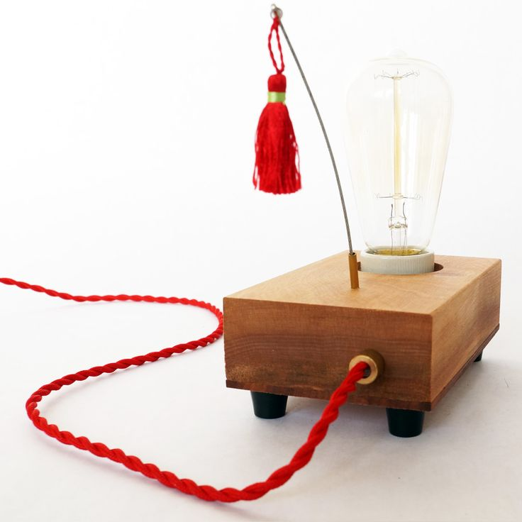 Lamp 'Tassel'.  The lamp is handcrafted in small series of oiled wood. With the protruding steel cable, the lamp is switched on and off.