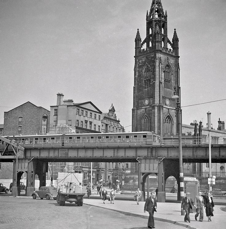 https://flic.kr/p/i9Ley4 | The Liverpool overhead railway | Who would have thought in 2013 a new and unpublished picture of the Liverpool overhead railway would come to light? Peter's picture is taken at an area known as Georges Dock Gates near James Street station. The train is a 27 from Seaforth and Litherland and is heading for Dingle. The railway opened in 1893 and closed 30th December 1956 a victim of the high cost of repairs. The road view gives a good snapshot of 1950's Britain…