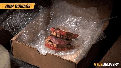 A pair of stained teeth riddled with gum disease sit in a delivery box with the Vyle Delivery logo