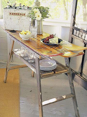 WATER SKIS and AN OLD LADDER:   A trio of now-landlocked water skis cruises to new heights as a handy serving table. The legs are made from sections of an old ladder. Barn boards create the storage shelf.