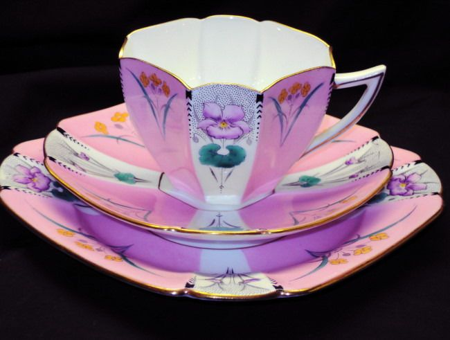 "Shelley (England) Queen Anne shape 'Pansy' pattern tea cup and saucer trio in pink, mauve, and green. Cup 2 3/8"" H, saucer 5 1/4"", plate 6 1/4"" all non-diagonal. Art Deco style."