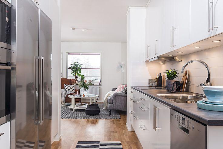 Modernt, stilrent och lättarbetat kök. Vit köksinredning av märket Ballingslöv, snyggt vitt kakel ovan arbetsytan och bänkskivor i mörkt utförande.