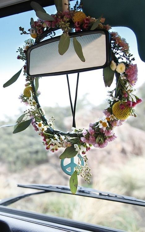 flower wreath and peace symbol on a car rear view mirror