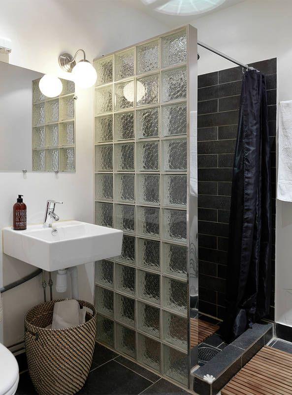 """Ścianka z luksferów wyznacza strefę natrysku w tej łazience. A do tego pozwala światłu z kinkietu przy lustrze przenikać do """"kabiny"""". Czarne kafle, zasłonka prysznicowa i ozdobny kosz dodają oszczędnemu wystrojowi elegancji."""