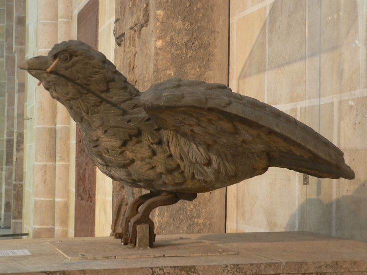 """""""Ulmer Spatz"""" (""""The Ulm Sparrow""""):  the original of 1858 by the cathedral roof is now in the Ulmer Münster near the entrance in a display case.  The Ulm Sparrow (Ulmer Spatz) is a landmark in and symbol of the German city of Ulm.  According to legend, the inhabitants of Ulm needed a particularly large beam for the construction of Ulm Minster, but could not get it through the city gate. As they were about to tear the gate down, they noticed a sparrow carrying a straw for its nest; which…"""