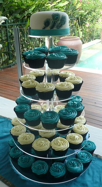 peacock wedding cupcakes. Maybe not peacock but I love the idea of a cup cake tower!