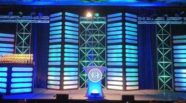 Our Bradford Panels can come in a wide range of covers like these industrial facades. Blended with our unique Space System Truss, this stage set is sure to wow. Our Stretch Fabric Podium adds a beautiful lighted centerpiece. #design #events #corporate #staging #liveevents #liveshow #production  #eventplanning #event #creative #custom  #branding #logo #brand #modular