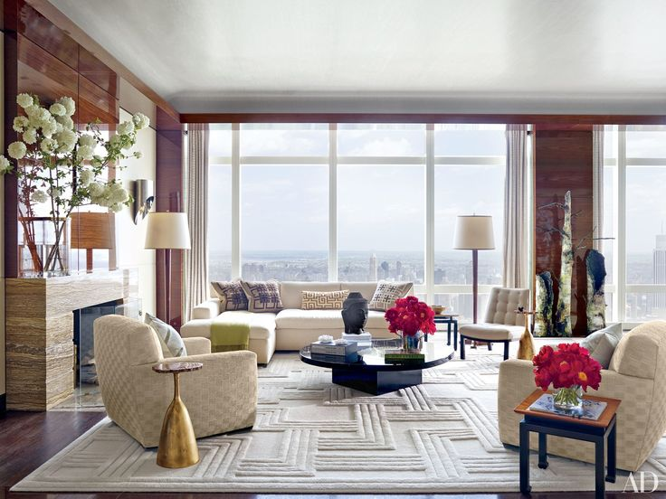 In jewelry designer Kara Ross and developer Stephen Ross's New York apartment, designed by Ingrao Inc., breathtaking city views unfold across the living room's floor-to-ceiling windows, which are curtained in an Armani/Casa fabric. The 1940s French mahogany floor lamps are from L'Art de Vivre, the papier-mâché sculpture of birch tree trunks is by Kim Krans, and the carpet is by Edward Fields.