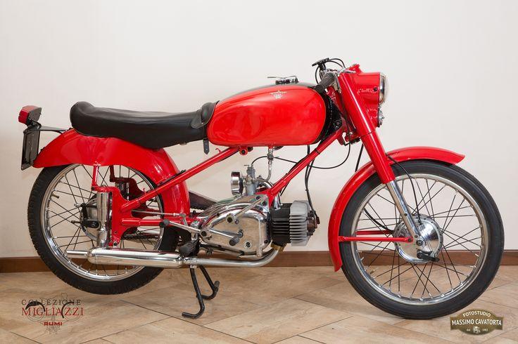 MOTO RUMI SPORT Nazione: Italia Tipologia: Sport Anno: 1955/1956 Tipo di motore: Bicilindrico a 2 tempi Cilindrata: 124,68 cc Potenza: 7 CV  Cambio: 4 marce Velocità massima: 100 Km/h Colore: Rosso con fascia nera sul serbatoio