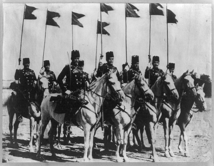 8 members of the Turkish cavalry on horseback with flags during the Balkan Wars