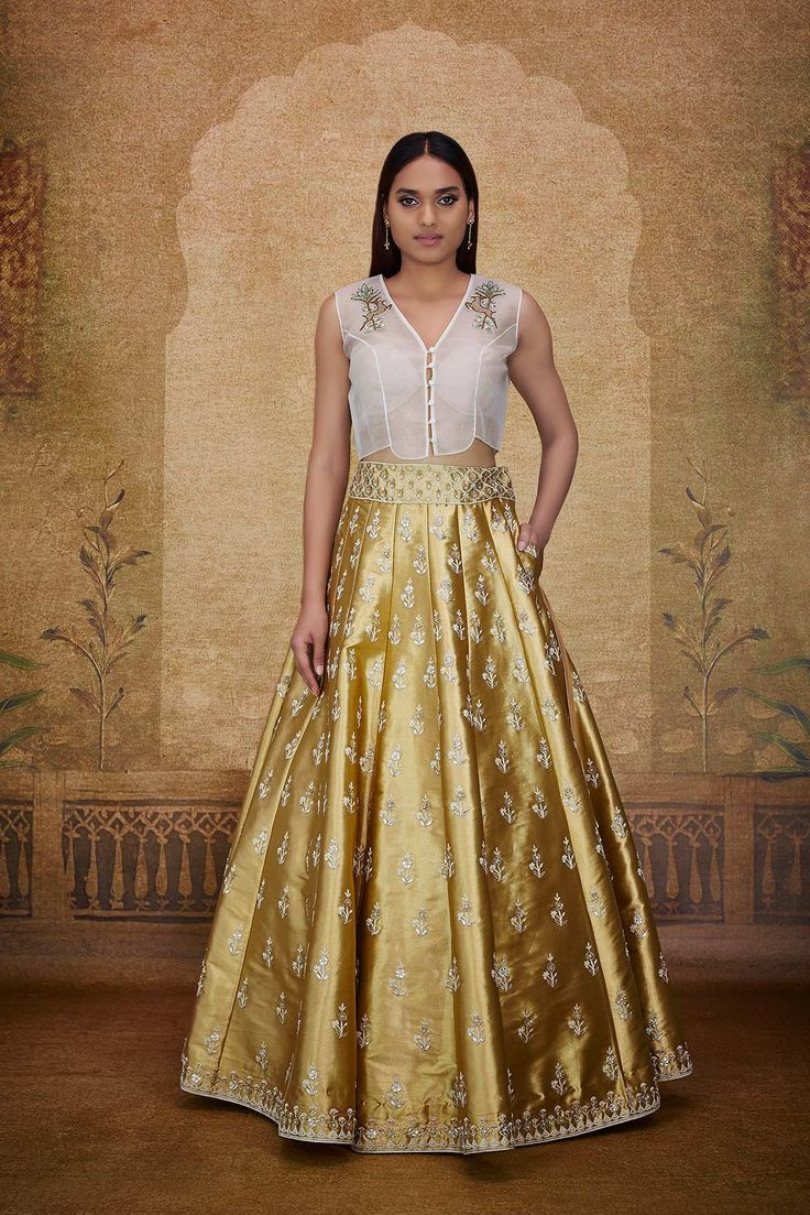 A natural organza crop top with extended shoulders and a V-neck, with delicate zari and dori embroidery in floral and deer motifs, paired with a flared A-line gold tissue lehenga exquisitely embroidered with gota patti, zardosi, resham and pearl work in floral butti motifs inspired by a whimsical land where the lush forest and glistening desert merge into one to find a universal elixir.