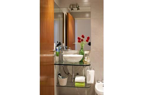 En modo dúplex: dos espacios pensados para una pareja joven  A fin de darle al baño un aspecto más moderno y liviano, se cambió el lavamanos por una mesada y un estante de vidrio con sostén de acero inoxidable (Open Glass) con una bacha de apoyo porcelana (Diseño Baño).
