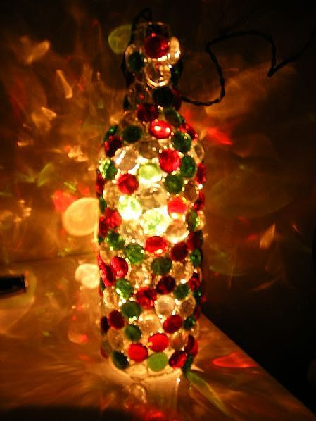 Bottle with Christmas lights inside and glass stones glued to the outside...I'm thinking this would be a great thing to do with glass blocks as well. LOVE this idea!! So inventive!