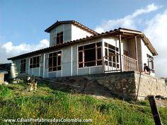 Casa en obra gris de dos niveles, en la parte superior una alcoba, se aprecian los perfiles que conectan las placas, ventanas y puertas en madera.