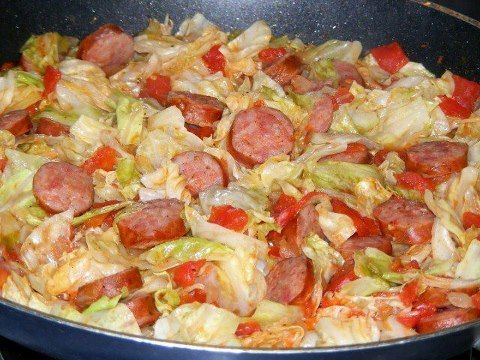 FRIED CABBAGE WITH SAUSAGE ... 1 stick butter, 1 small head of cabbage, chopped,  1 small onion, chopped, 1 lb polish sausage, sliced into round pieces, 1 (15 ounce) can diced tomatoes,  1/2 teaspoon salt, 1/2 teaspoon pepper, 1/4 of green pepper, few drops of hot sauce (opt.)  ...  Melt butter in lg skillet. Add cabbage, onion, & gr pepper, cook on med high for 5 min.  Add remaining ingredients, cover and simmer for 20 – 25 minutes. Makes about 8 servings.