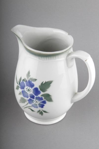 Forssan museo 6955:61. Arabian valkoinen KB-mallin kannu, jonka yhdelle kyljelle on maalattu sini-vihreä kukkakuviointi. Astian piippuleima asettaa astian valmistusajankohdan vuosien 1932-1949 välille, jolloin Arabia painoi astioihinsa ikonisen piippuleiman. http://www.piipunjuurella.fi/objectinfo.php?id=121056&image_id=121724&viewimg=1&prms=