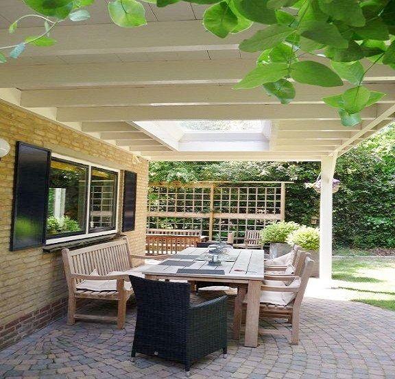 Klassieke houten veranda aan huis met plat dak lichtkoepel lichtstraat van lariks douglas eiken hout zelfbouw bouwpakket wijchen