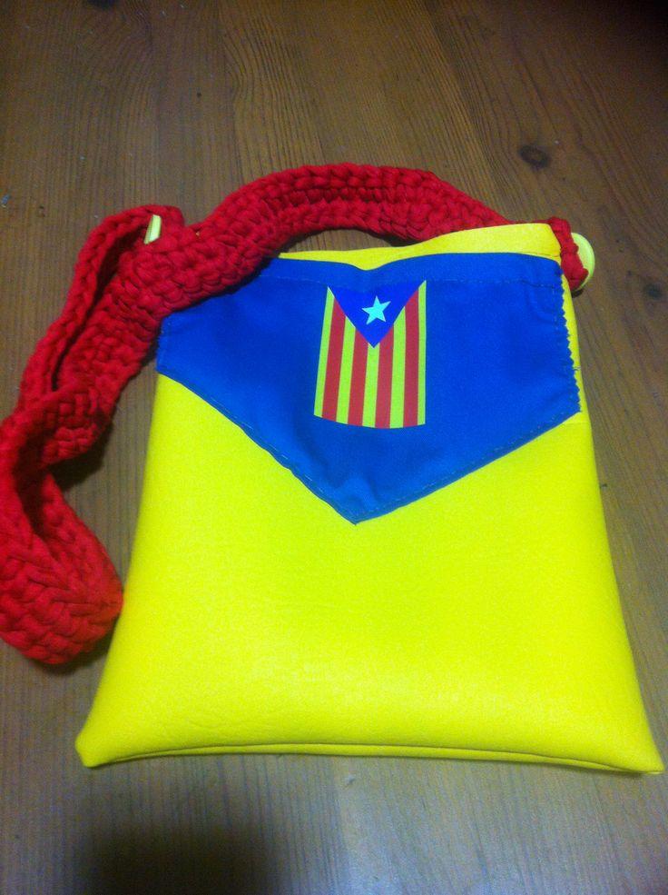 Teresa; tela plastificada amarilla con bolsillo de tela azul y la bandera catalana como pegatina decorativa. Tira de trapillo rojo. Cierre de bercro.