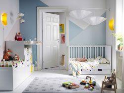 Ein Kinderzimmer mit STUVA Babybett mit Schubfächern in Weiß, einem Wickeltisch und einer Banktruhe mit einer großen Schublade auf Rollen