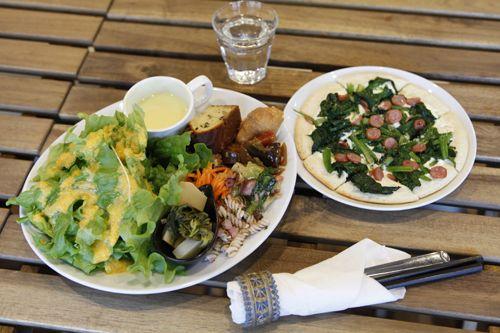 ●この日のサラダプレート(グリーンサラダ、ナスとパプリカの味噌炒め、レンコンとセロリのラグー、ケークサレ、梅ごぼう、青野菜とタコ・桜エビの煮物、紫ニンジンのショートパスタマリネ、ニンジンサラダ、菜花とたけのこの土佐煮)。●ひとくち野菜スープ(さつまいものポタージュスープ)●タルトフランベ(ほうれん草のソテーとソーセージ)。※毎日総菜のメニューは変わる。※タルトフランベも通常3種類から選べるCafe TAMAE