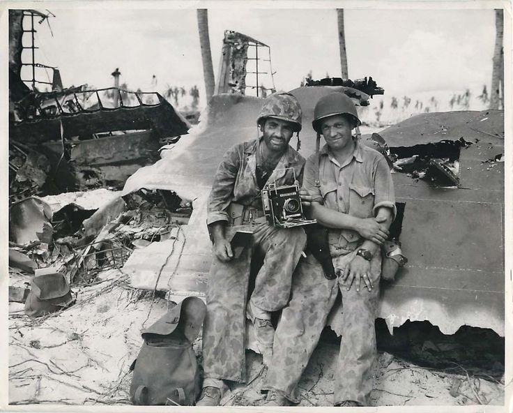 1943- U.S. Marine combat photographers Corporal Obie R. Newcomb and Corporal Raymond Matjasic, posing beside the wreckage of a Japanese plane on Tarawa.