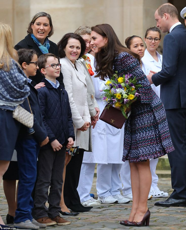Dazzling: Kate greeted Parisians who turned out to meet her at the military hospital carrying a Chanel purse