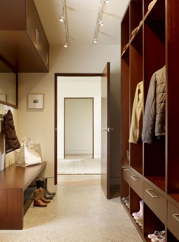 Open storage closets made with drawers and shoe cubbies keep the family organized in this small modern mudroom. On the opposite wall is a built-in wood bench, and hanging above it is a mirror with small hooks and additional wall-mounted storage cabinets.