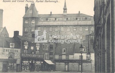 The Square and Symington's Factory, around 1900.   This is the first Symington corset factory, situated on Factory Lane and viewed from across the square. The factory building was originally a carpet factory in 1805 and in 1865 it was partly occupied by Robert and William Symington to produce their corsets. By 1877 it was fully occupied by the Symingtons and in 1881 three more floors were added. The building was demolished in 1973.