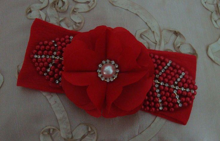 Faixa em meia de seda vermelha com linda flor em cetim e folha bordadas com pérolas e strass para encantar suas princesas.