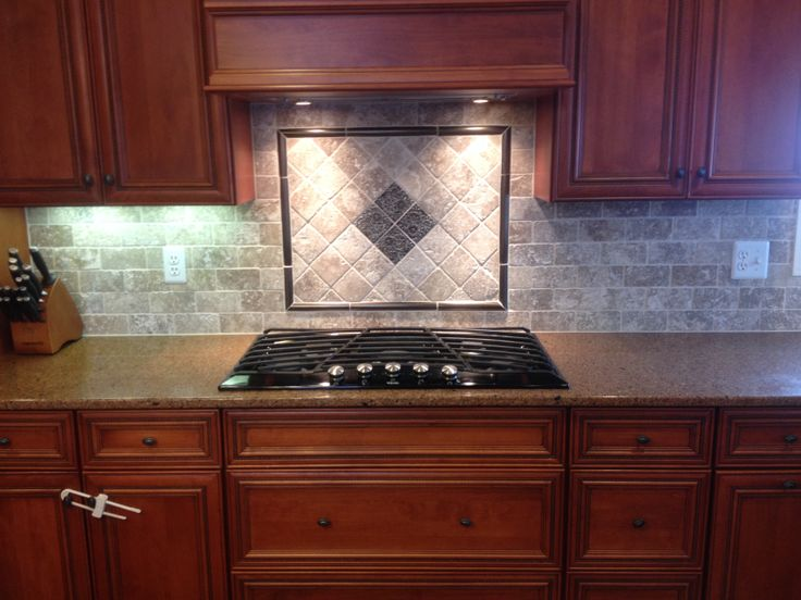 New Tile Backsplash With Mosaic Design Behind Cooktop In