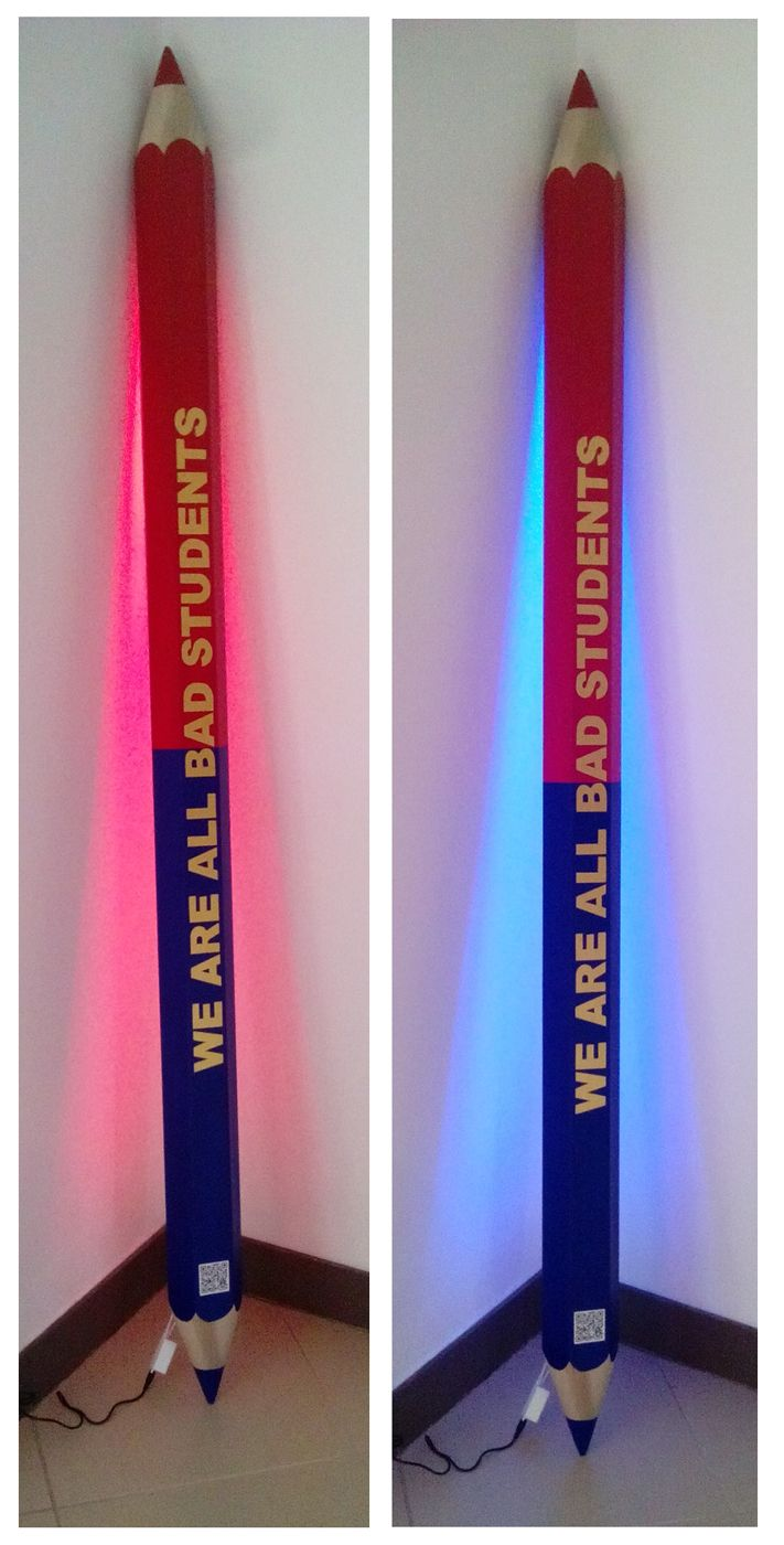 A message in a pencil: we are all bad students.  Sculpture Led Lamp Wood, paint, led and qr code 200 cm h 2016