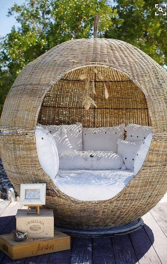 A circular wicker small room with padding and pillows inside