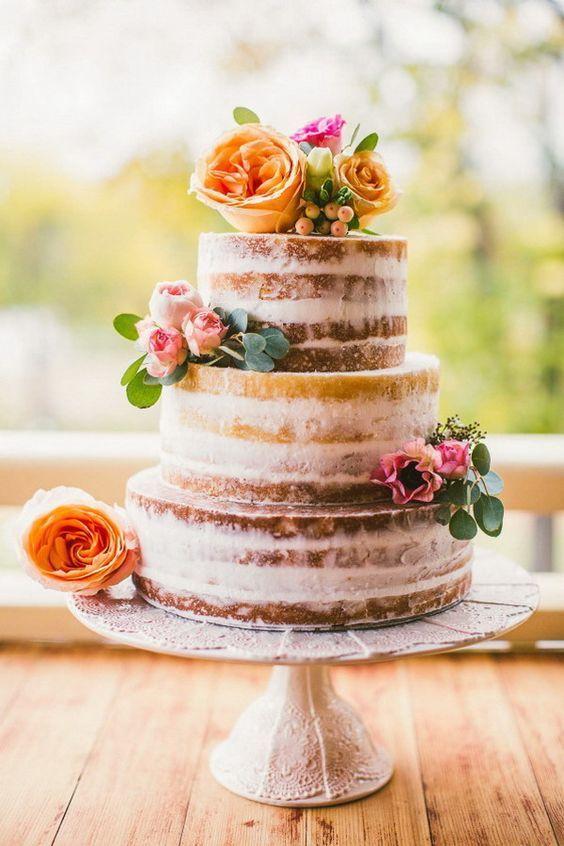 Tendencias en pasteles de bodas para este año: ¡Vivan las tartas semi-desnudas! Pastel rústico cubierto con una capa fina de crema de mantequilla, adornado con rosas frescas de distintos colores que se complementan.