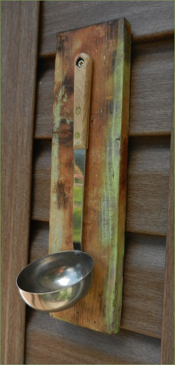 ladle mounted to a old piece of board. (bird feeder) add half orange, grape jelly, birdseed or water.