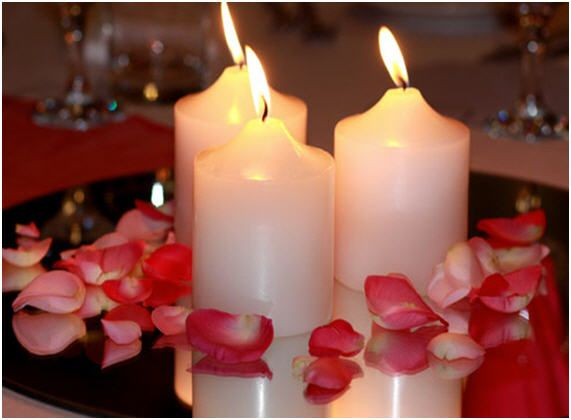 Wedding centerpieces use a mirror and flower petals for