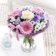 This is a traditional bunch of flowers with a collar on mothers day. It uses pastel colours and flowers.