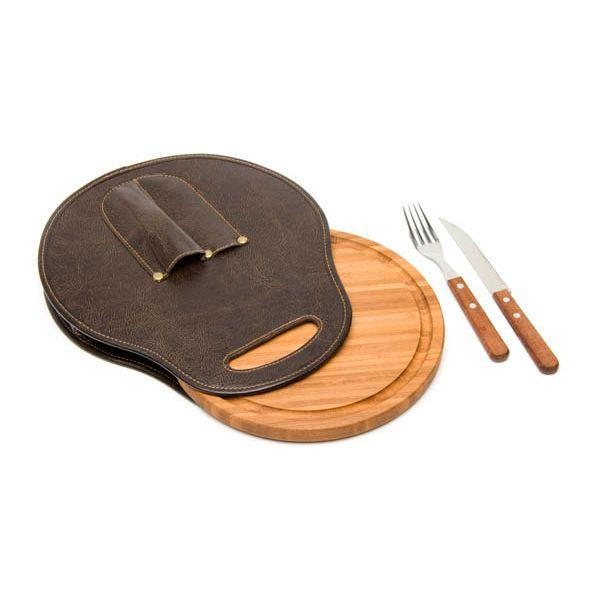 COD.VN032 Original set de asado individual que incluye plato de bamboo con decantador, juego de cubiertos (cuchillo y tenedor Tramontina ®) con mango de madera y un contenedor del set en cuero ecológico marrón, cuyo formato se asemeja a un estribo para caballo. Medida del plato: 23 cms de diámetro. Medida del estribo: 26 cms x 30 cms.