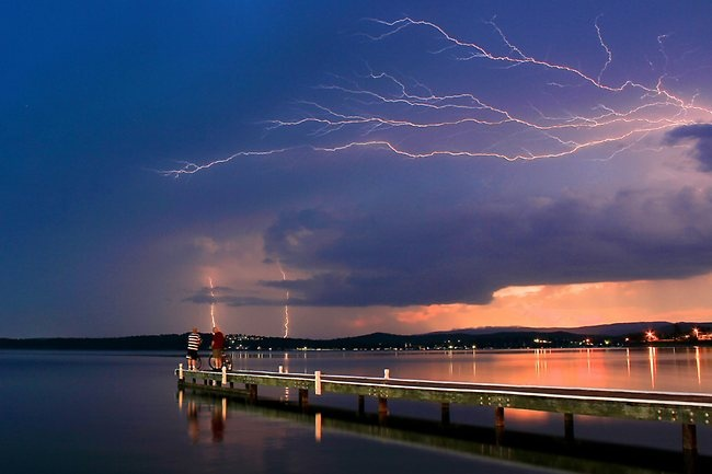 Watching an approaching storm across Lake Macquarie in November 2011. Picture: PETER KENNELLY, Warners Bay, New South Wales, Australia