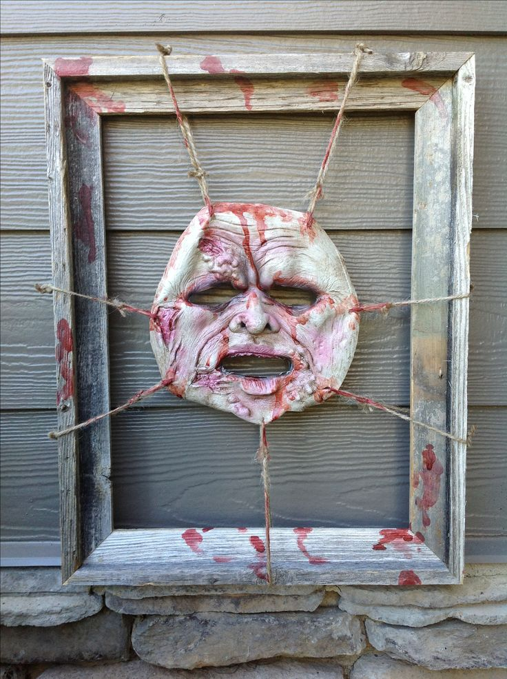 Halloween mask prop - Easy to make: Just tie a latex mask to an old wooden frame, add spray paint, then splatter with fake blood!