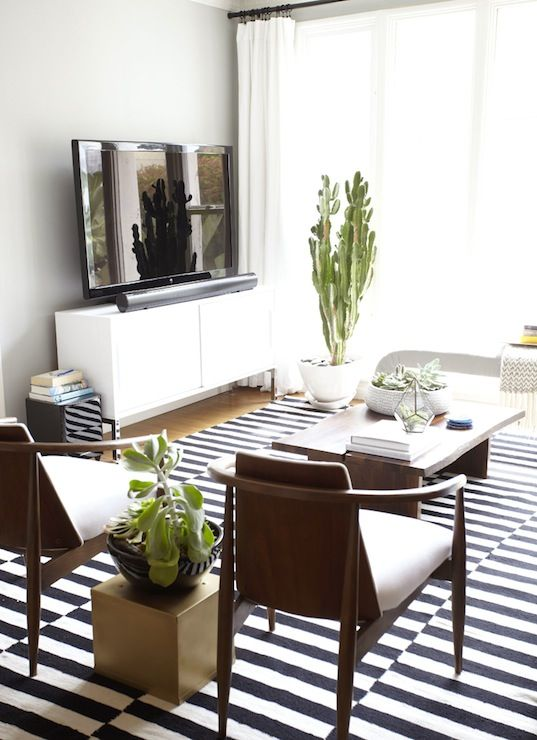 A Striped Rug Pops In The White Sunny Living Room Two Small Chairs Surrounded By Plants Offer Extra Seating Without Overpowering Space