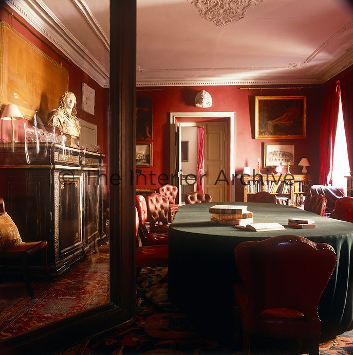 A red dining room with red leather chairs placed around an oval tablel with a green cloth covering. A bust, glassware and lamps are arranged on top of an antique cabinet. A brass picture rail is mounted on the wall below the cornicing.