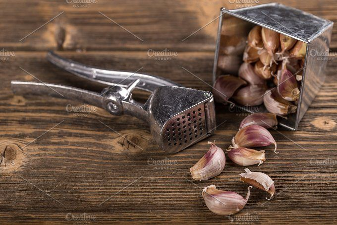 #Garlic  Garlic and garlic press on rustic wooden background