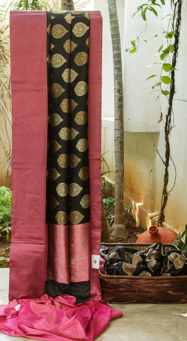 BLACK BENARES SILK IS ENHANCED WITH PINK AND GOLD TISSUE BORDER AND PALLU. THE TRADITIONAL MOTIFS IN GOLD AND ANTIQUE GOLD ACCENTUATE THE SAREE.